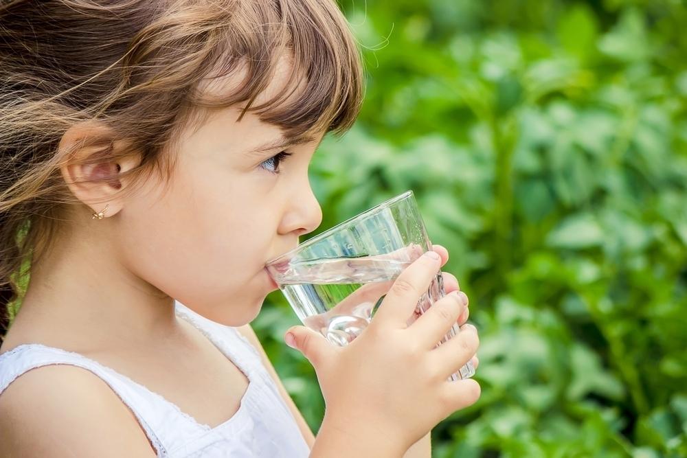 fille boit un verre d'eau